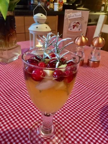 Rosemary infused white wine and apple juice sangria with sprigs of rosemary and cranberries.