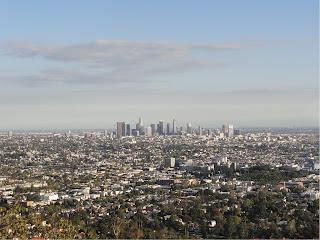 Utsikt over en stor by med hovedsakelig lave bygninger. En samling av skyskrapere midt i bildet.