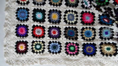 Crochet granny square blanket, 3 layers of colour in centre surrounded by black then white to make up each square. These have then been sewn together to form a blanket. Blanket then edged with white lace stitch. The colours in the squares are completely random