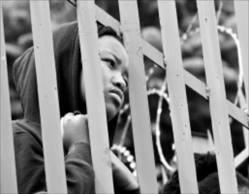 NOT IMPRESSED: A non-protesting University of Johannesburg student watches demostratios from behind a security gate. Pic. Bafana Mahlangu. 04/03/2010. © Sowetan.