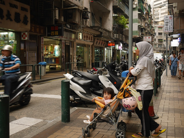 girl in stroller pushed by woman wearing a hijab in Macau's Three Lamps District