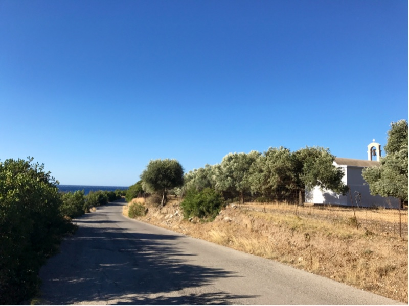 Smal vei som går mot havet i det fjerne. En liten, hvit kirke på høyre side av veien.