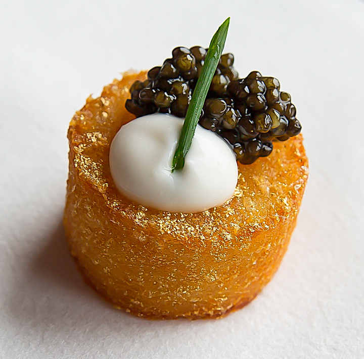 photo of a potato bite topped with crème fraîche and caviar