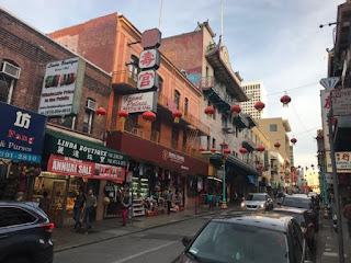 Gate med eldre bygninger, kinesiske tegn på butikkskiltene og runde, orange lykter som henger over gaten.