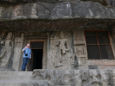 A white man standing in the entrance to a buddhist cave at Ellora