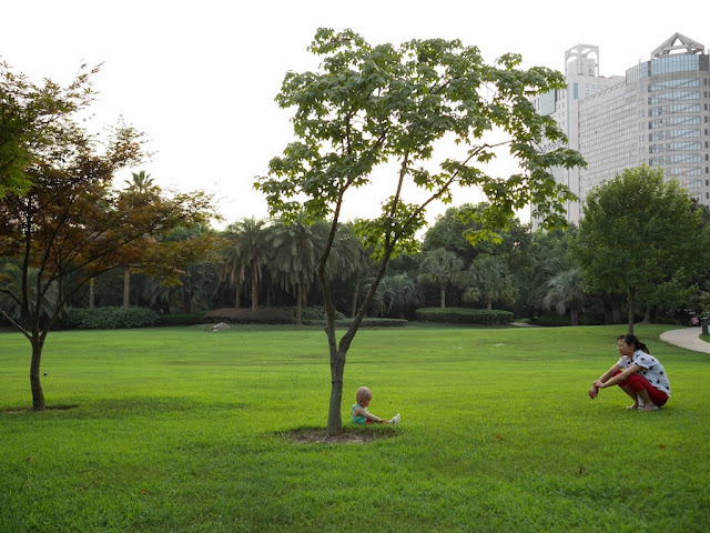 woman watching a child sitting on the grass at Yanzhong Green Space (Square Park) in Shanghai
