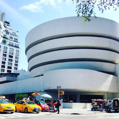 The Exterior View of the Guggenheim, design by Frank Lloyd Wright, from the other side of Fifth Avenue - with Yellow NYC Cabs in front, even!