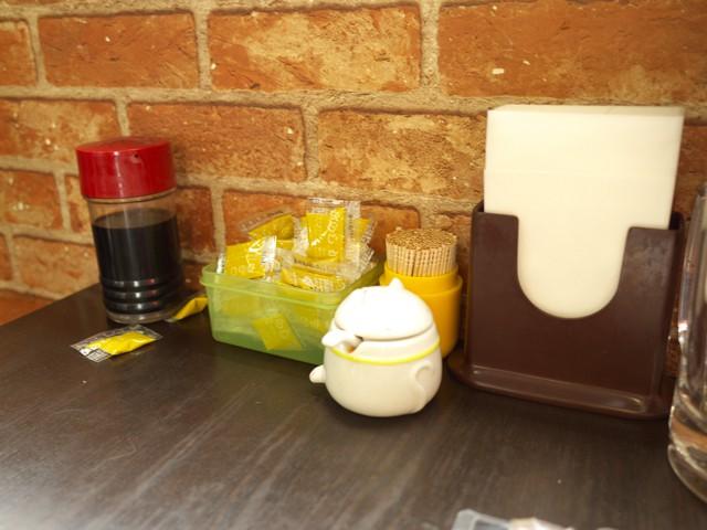 テーブルの上に置かれたウスターソースと袋入りのカラシ