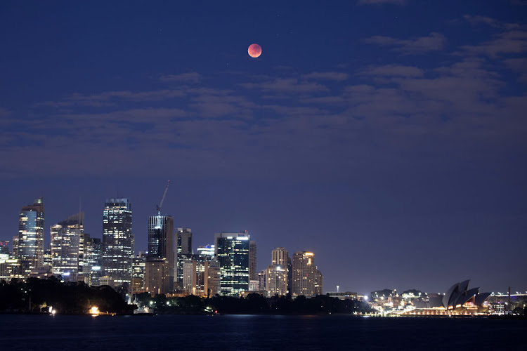 The moon is seen turning red over the Sydney skyline during a total lunar eclipse on July 28 2018 in Sydney, Australia.