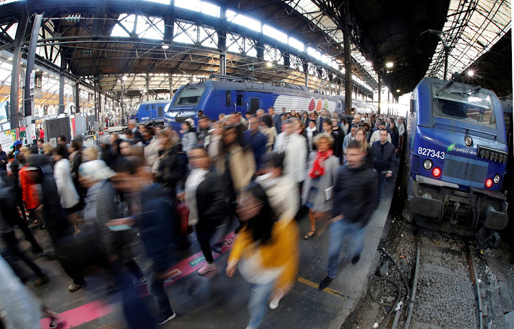 Commuters walk on a platform after they arrived at the Saint-Lazare train station in Paris during the tenth day of a nationwide strike by French SNCF railway workers.
