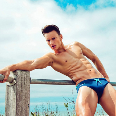 Hot guy in a blue speedo on the beach