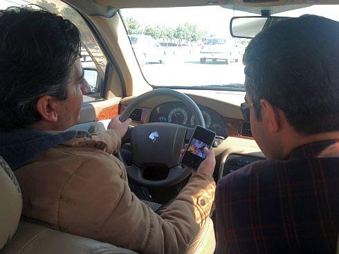 Taxi-Fahrer zeigt Beifahrer Familienfotos auf der Autobahn in Teheran