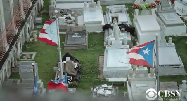 Screenshot from the CBS News video, 'Puerto Rico: The exodus after Hurricane Maria', showing the flag of Puerto Rico flying over a cemetary. Photo: CBS News