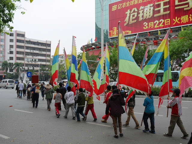 people carrying multicolored striped flags across a street in Maoming, China