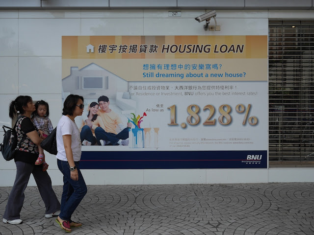 two women with a little girl walking by an advertisement for housing loans