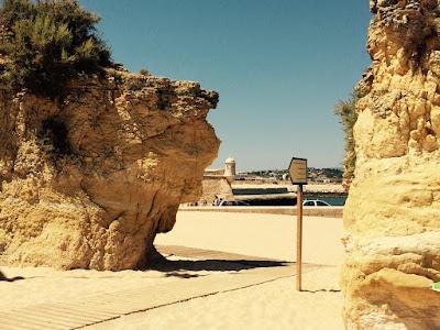 En sti på stranden mellom to klipper.
