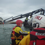 Lifeboat and fire crew look on as the Jenkins Marine crane prepares to lift the submerged vehicle - 27 October 2014.  Photo credit: RNLI/Poole