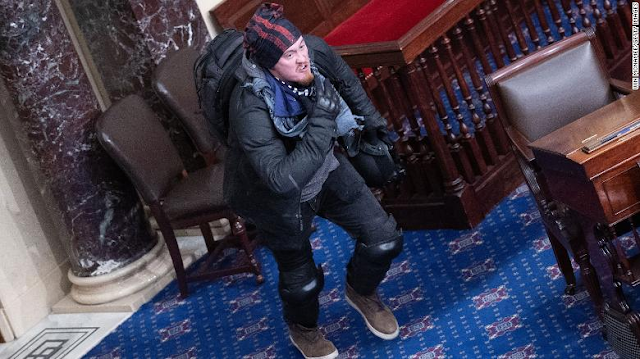 Man seen hanging off Senate balcony and sitting in Vice President's chair during Capitol riot is in custody