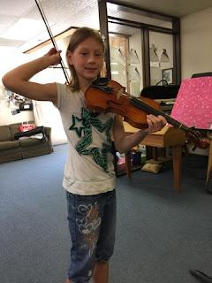 student uses violin bow as backscratcher