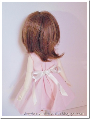 A pink vintage style dress set for a doll.