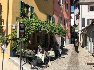 En smal, brolagt gate med noen bord under et tak av eføy inntil den ene veggen.