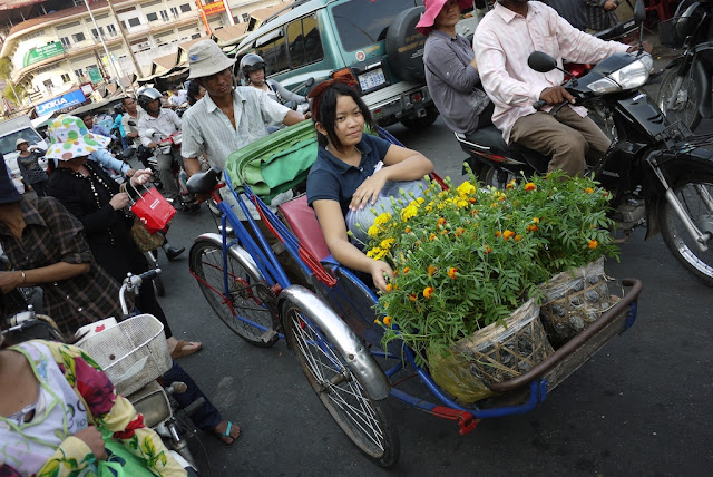 young woman with many flowers riding a pedal-powered rickshaw in Phnom Penh, Cambodia