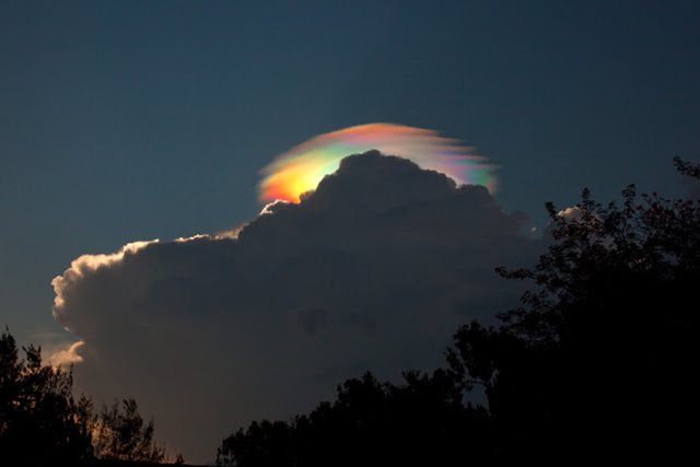 A dark cloud over a forest scene - above and behind it is a brightly lit cloud showing bright rainbow colours