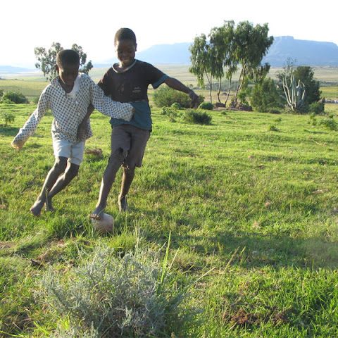 Children in Lesotho play football with a plastic bag ball