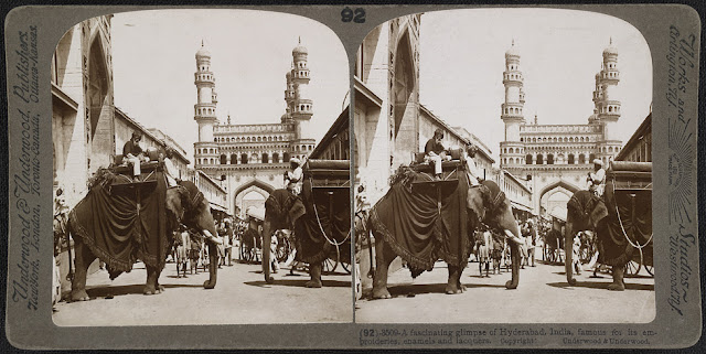 "Stereographic photograph of Hyderabad in Andhra Pradesh, taken by James Ricalton in c. 1903, from The Underwood Travel Library: Stereoscopic Views of India. Hyderabad was founded beside the River Musi in 1591 by Muhammad Quli Qutb Shah (r.1580-1612) as an alternative to his capital at Golconda. The town was laid out in a grid pattern with two main roads running east to west and north to south; the Char Minar sits at the intersection of these two roads. The Char Minar, or Four Towers, seen in the background of this view, was built in 1591 to mark the centre of the city. This ceremonial structure comprises four imposing arched portals with arcaded storeys and geometric screens above. The four corner minarets are crowned with domical finials. They contain spiral staircases opening onto triple tiers of balconies. This image is described by Ricalton in 'India Through the Stereoscope' (1907), ""Two of the Nizam's state elephants have intruded athwart the street and obstructed our view...These"