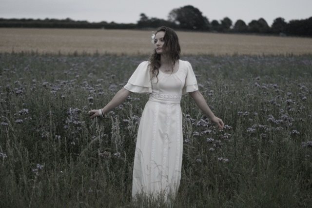 bridal inspiration seventies style dress in a field