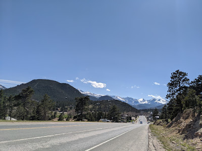 A four lane roadway wanders down toward tall green and white peaks in the distance.