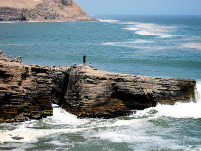 Man jumping off a cliff by El Salto del Fraile restaurant in Lima Peru