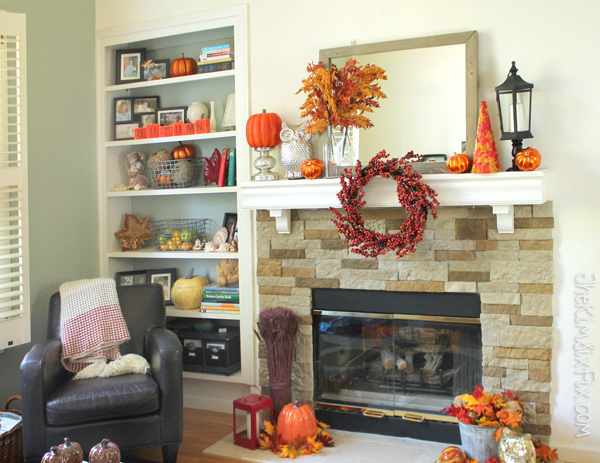 A gorgeous fall mantel in oranges and reds with accent pops of silver and black.  I love how the wreath is hung off the front of the mantel shelf!