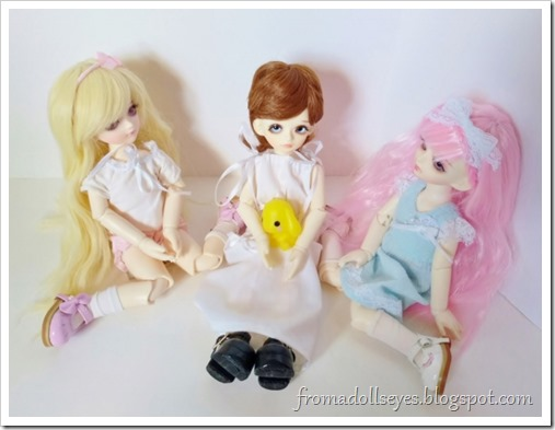 Three little yosd sized ball jointed dolls sitting nicely together.  On the left is the blond haired noisy bjd (Sakura), and the right is the pink haired quiet bjd (Yuna).  Sitting between them is a little boy bjd with brown hair.  He is wearing a long white dress that's too big (it's the only clothes we had) and holding his yellow toy bunny.  We will discuss his new name today.