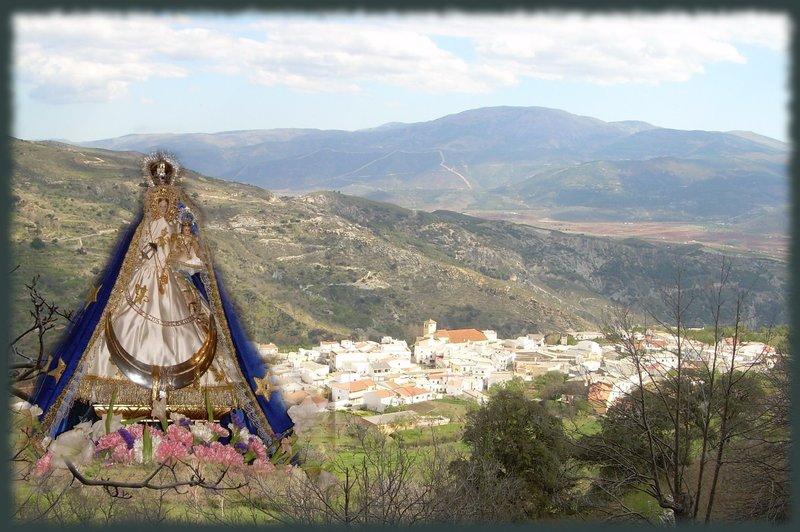 Imagen de la Virgen de los Remedios, patrona de Paterna del Río, con el municipio al fondo