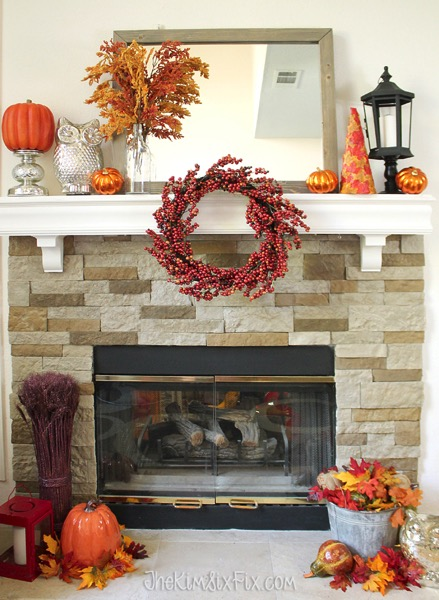 A gorgeous fall mantel in oranges and reds, featuring a berry wreath and metallic silver accents