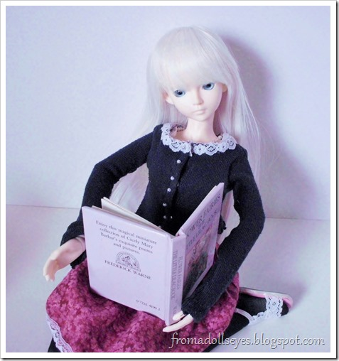 A ball jointed doll reading a tiny book about flower fairies.