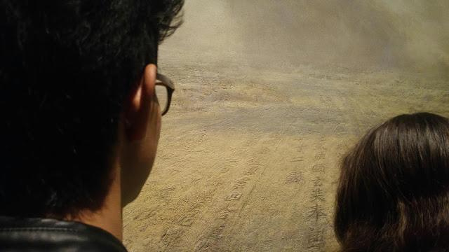 Foto de dos jóvenes mirando un cuadro de arte, creando un efecto donde ellos forman parte de la pieza