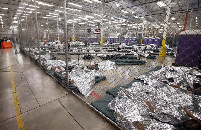 Detainees sleep and watch television in a holding cell where hundreds of mostly Central American immigrant children are being processed and held at the U.S. Customs and Border Protection (CBP) Nogales Placement Center in Nogales, Arizona, U.S. 18 June 2014. Photo: Ross D. Franklin / REUTERS