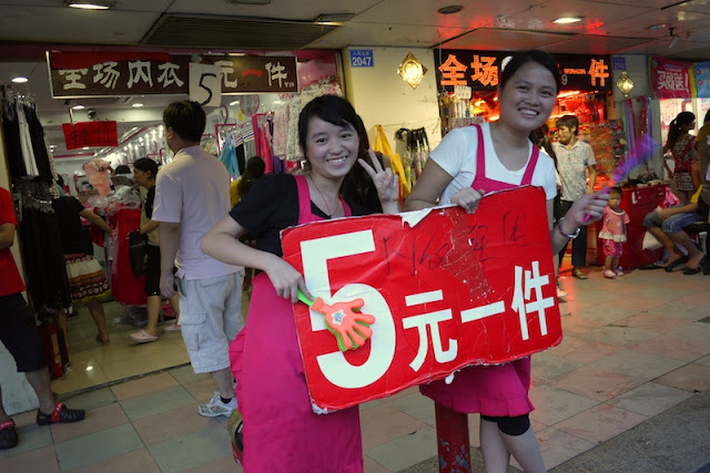 two young women hold a sale sign in front of a store at Dongmen in Shenzhen, China