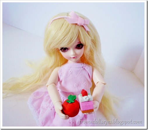 A ball jointed doll trying to choose between a healthy apple and cake.