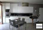 cucina Ola Snaidero con penisola a forma di boomerang e piani in quarzo nero, tavolo Convoy Calligaris e sedie Air hight Calligaris, consegnata in provincia di Bergamo