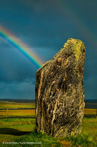 A standing stone with two rainbows in the background