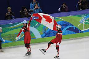 Charles Hamelin and Francois-Louis Tremblay celebrating their gold and bronze medal-winning races