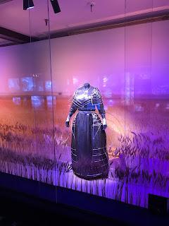 Sort kjole med metalldekor bak et glassmonter. Skal se ut som den står i en åker.