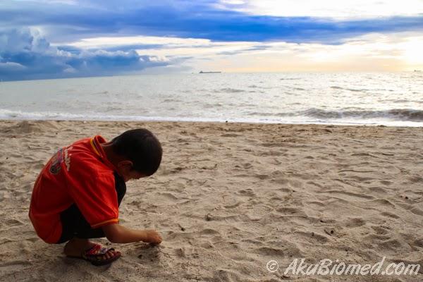 Abang Ngah bermain pasir sementara menunggu matahari terbenam