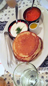 Zakuski, variety of Russian drinking appetizers at DaNet. Traditional Blini served with sour cream and dill, melted butter and seawater cured caviar