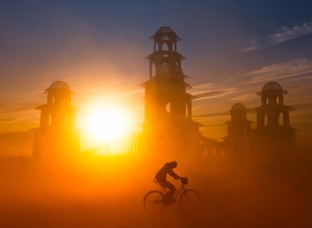 bersepeda melintas di tengah gurun penuh pasir, matahari terbenam