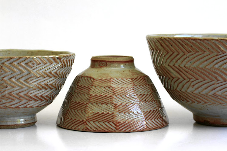 Christo Giles uses cheese slicers with different wires attached to facet and make zig-zag patterns on his pots.