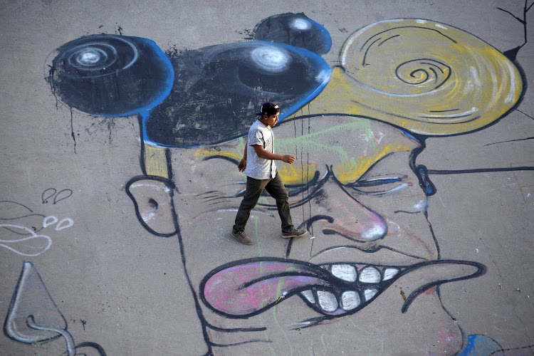 A man walks over a graffito mocking U.S. President Donald Trump at the Mexican side of the border in Ciudad Juarez.